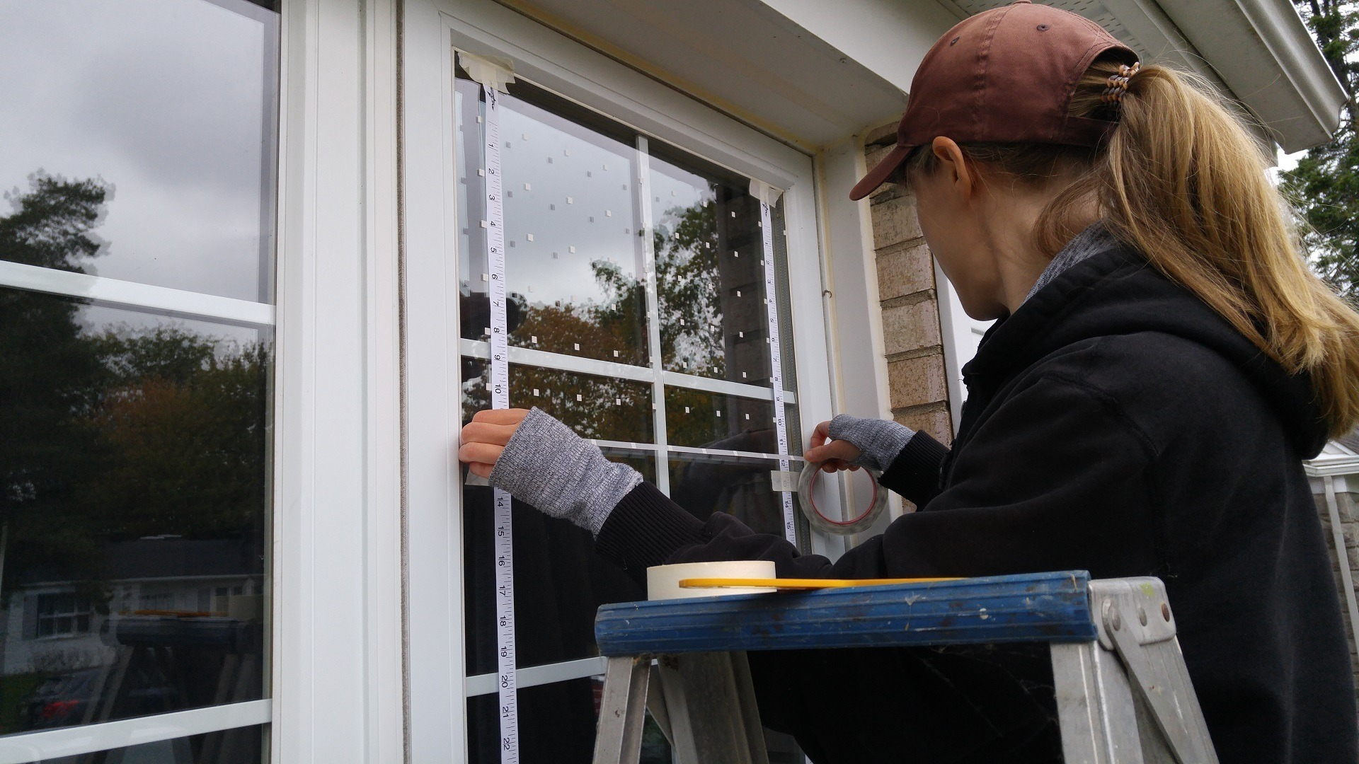A woman installing decals on her windows for preventing bird-window collisions