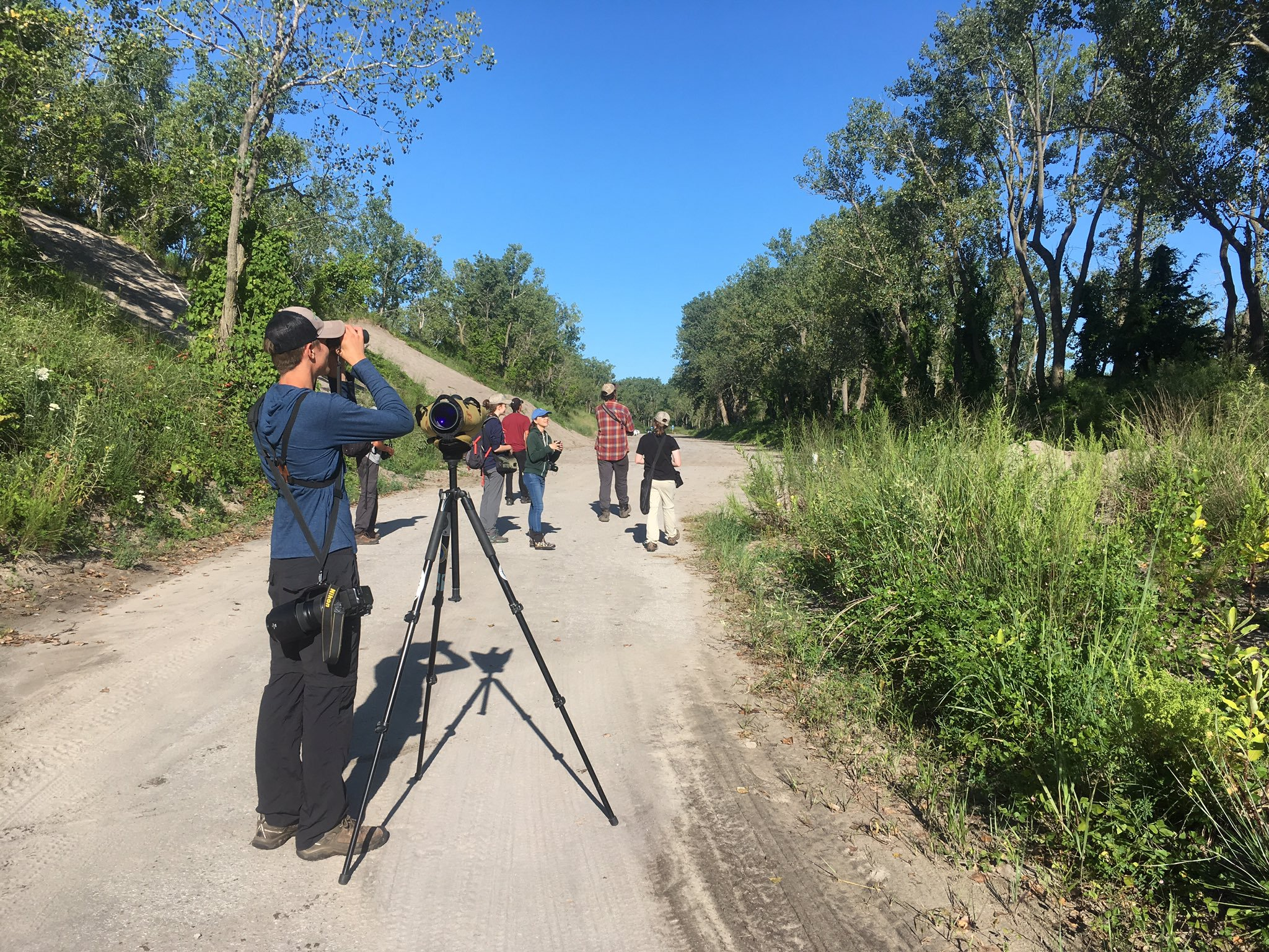 A group of young birders watching birds on a dirt road