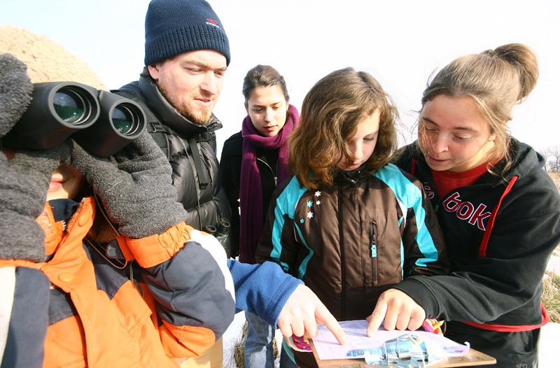 A group of kids gathered to look at a checklist of birds for the Christmas Bird Count for Kids